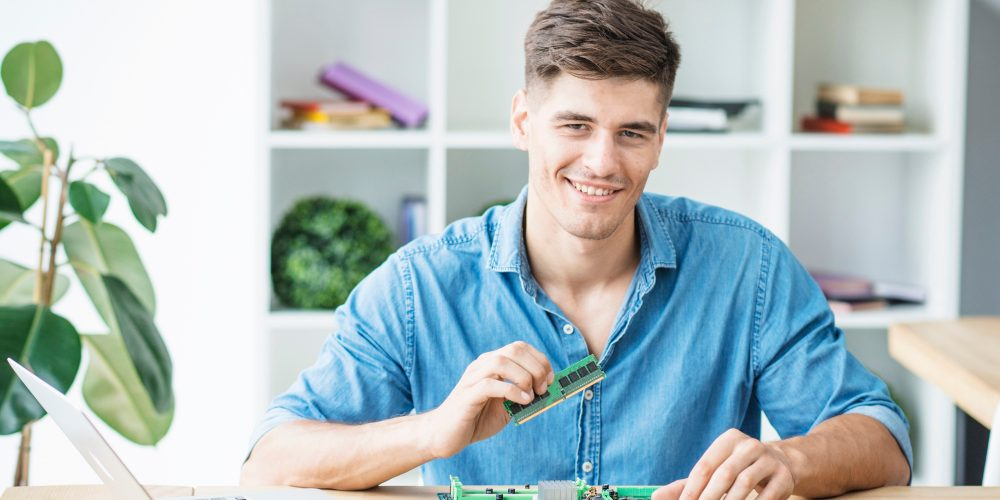 smiling-young-male-it-technician-with-hardware-equipment-s